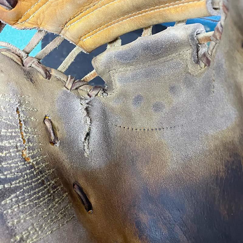 キャッチャーミットの破れ修理(皮革を当てた部分に紐を通す穴を開ける)・修理前